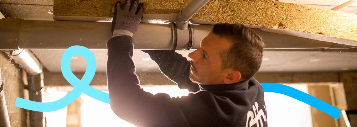Artisan posant isolant entre plafond et canalisation