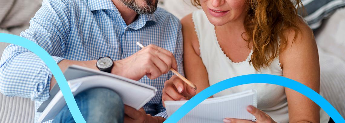 Couple comparant leurs notes sur leur cahier