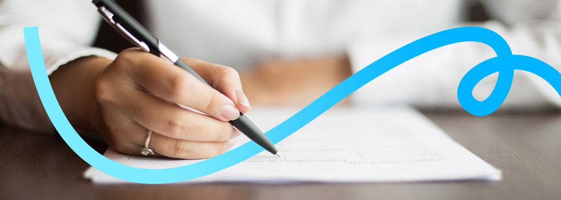 Main de femme portant une bague et signant avec un stylo noir un contrat