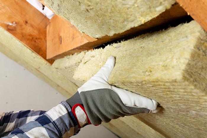 artisan posant un isolant sous un toit