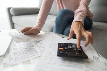 Femme tapant sur sa calculatrice avec des papiers