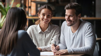 Jeune couple s'apprêtant à signer pour leur premier investissement