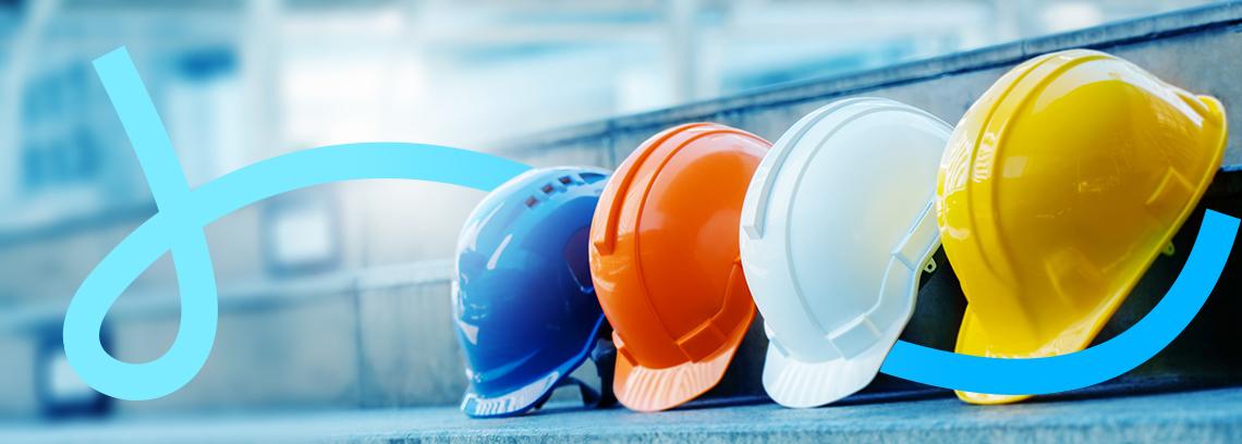 Quatre casques de chantier bleu orange blanc et jaune