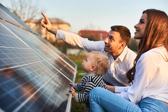 petite famille devant des panneaux solaires