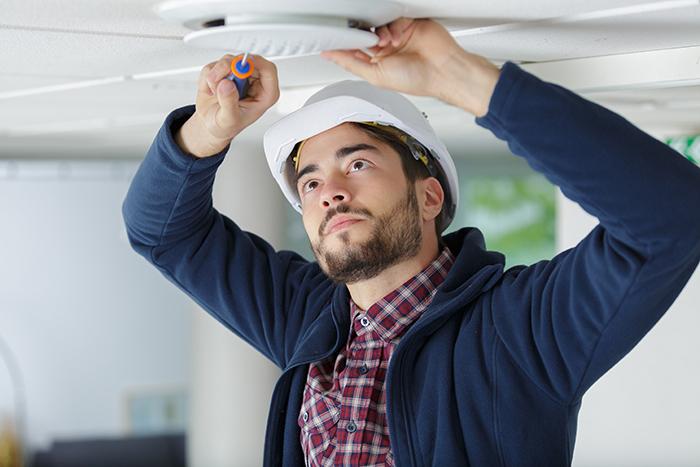 artisan qui visse une ventilation au plafond